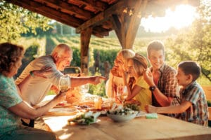 Grandfather pointing at wife while family eats dinner outside, children and their parents are laughing