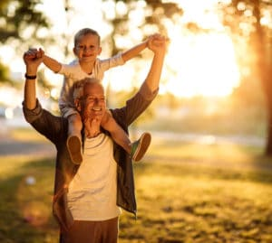 Older man smiles with grandson on his shoulders while sun rises in background