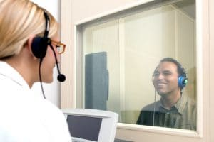 Man receiving a hearing test through headphones, sitting in a booth, looking at a female audiologist through a window.