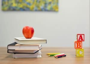 Books, blocks and an apple on a school desk
