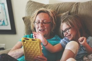 Woman and girl sitting in a recliner playing with a tablet
