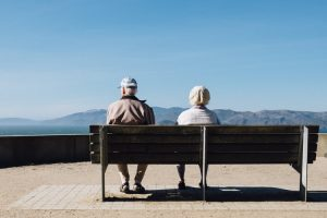 Older couple sit on a bench together.
